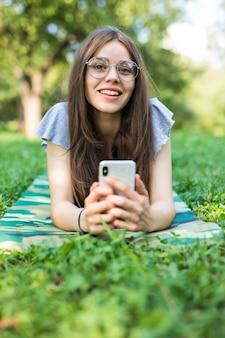 Erfreute brünette frau in brillen, die auf gras liegen und smartphone im park verwenden