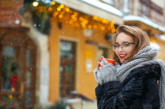 Erfreute brünette frau trägt strickschal und stilvolle brille, die schneefall genießt und kaffee trinkt. freiraum