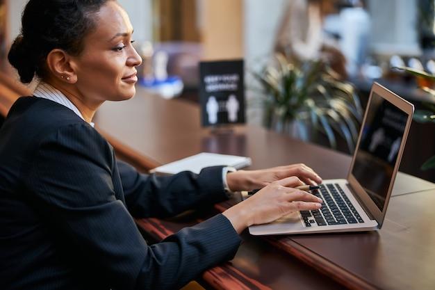 Erfreute brünette weibliche person, die ein lächeln auf ihrem gesicht hält, während sie auf den bildschirm ihres laptops schaut