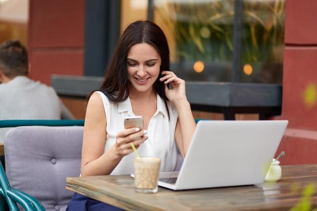 Erfreute dunkelhaarige frau hält modernes handy, liest positive nachrichten auf der internet-website, trinkt cocktail in der cafeteria im freien