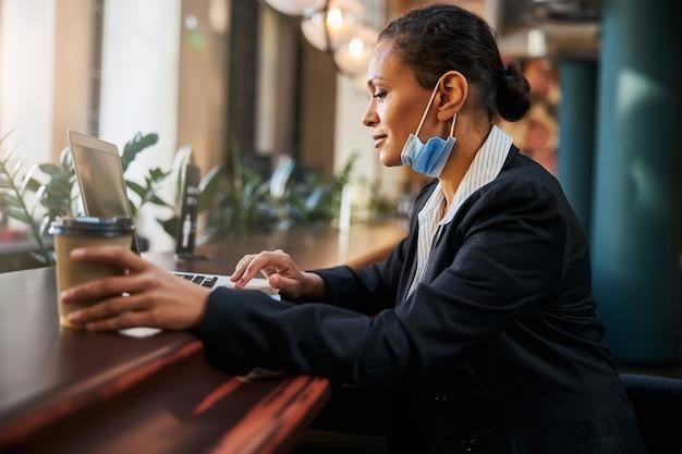Erfreute dunkelhäutige frau, die ihren laptop benutzt, während sie auf distanz zum café arbeitet working