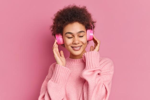 Erfreute dunkelhäutige junge frau hört gerne angenehme melodie hält hände auf stereo-kopfhörer schließt augen trägt lässigen pullover