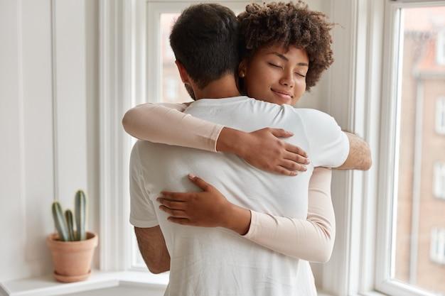 Erfreute dunkelhäutige junge frau umarmt ihren freund herzlich, freut sich, posiert am fenster, hat eine romantische beziehung, steht in einem gemütlichen raum. ehemann und ehefrau fühlen sich zufrieden und zusammen