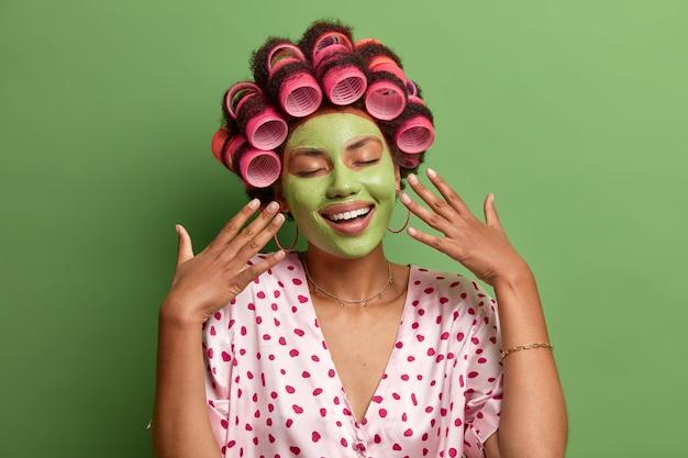 Erfreute entspannte hausfrau steht mit erhobenen händen, geschlossenen augen, sanftem lächeln, trägt feuchtigkeitsspendende grüne maske auf gesichtshaarrollen auf und bereitet sich auf eine großartige veranstaltung in häuslicher kleidung vor