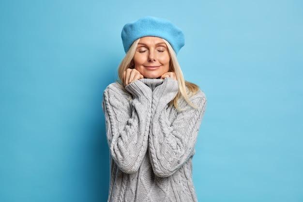 Erfreute erwachsene frau trägt bequemen strickpullover hält hände auf kragenständern mit geschlossenen augen genießt friedlichen moment.