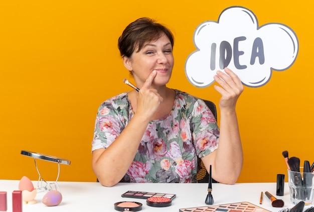Erfreute erwachsene kaukasische frau, die am tisch mit make-up-tools sitzt und ideenblase und make-up-pinsel hält