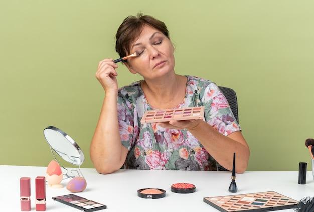 Erfreute erwachsene kaukasische frau, die mit geschlossenen augen am tisch sitzt, mit make-up-tools, die lidschatten-palette halten und mit make-up-pinsel auftragen