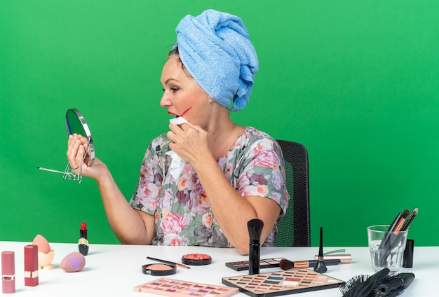 Erfreute erwachsene kaukasische frau mit eingewickeltem haar in handtuch, die mit make-up-tools am tisch sitzt, wischt sich den mund mit nasser serviette ab