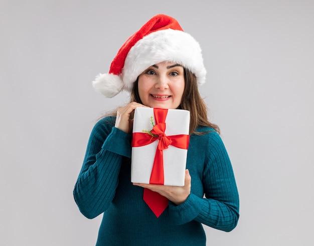 Erfreute erwachsene kaukasische frau mit weihnachtsmütze und weihnachtskrawatte, die weihnachtsgeschenkbox hält