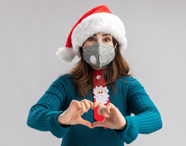 Erfreute erwachsene kaukasische frau mit weihnachtsmütze und weihnachtsmann-krawatte, die eine medizinische maske trägt und das herzzeichen einzeln auf weißer wand mit kopienraum gestikuliert