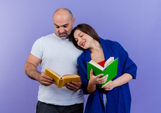 Erfreute erwachsene paarfrau in schal gewickelt, buch haltend und blick auf die buchfrau des mannes, die den kopf auf seine schulter legt