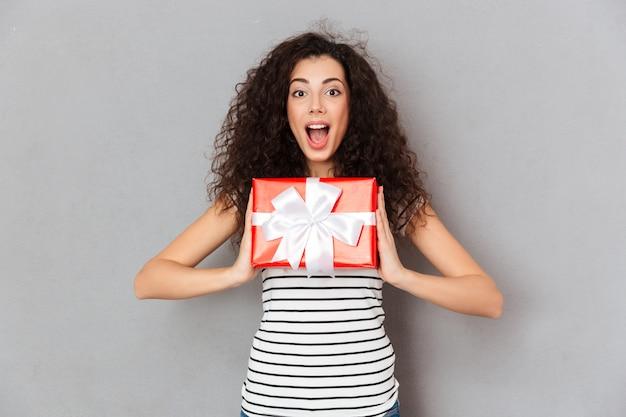 Erfreute frau 20s, die das geschenk des roten kastens eingewickelt aufgeregt und überrascht halten, um geburtstagsgeschenk zu erhalten