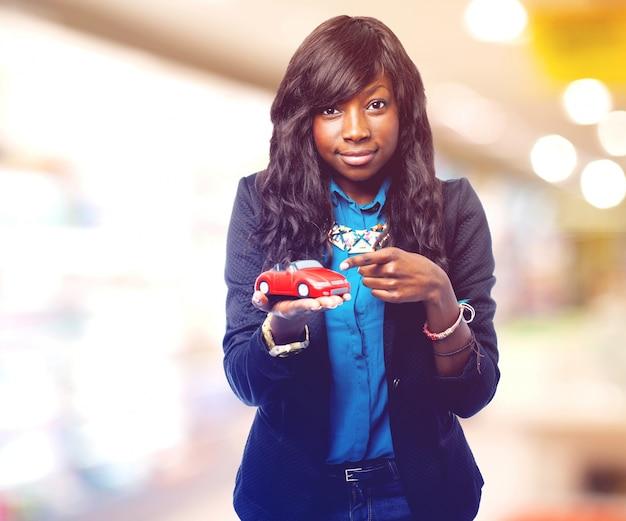 Erfreute frau, ein kleines auto auf ihrer hand zeigt