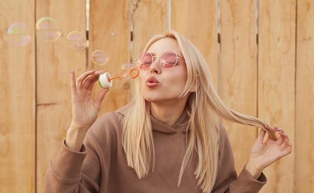 Erfreute frau mit blonden haaren und in trendiger rosa sonnenbrille, die seifenblasen bläst