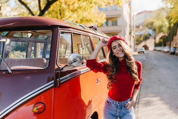 Erfreute frau mit herrlicher lockiger frisur, die zeit draußen im sonnigen oktobertag verbringt und lächelt