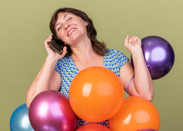 Erfreute frau mittleren alters mit bunten luftballons, die fröhlich lächeln, während sie auf dem handy telefoniert
