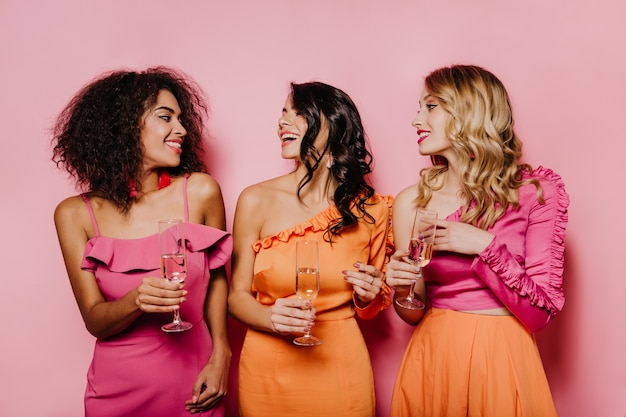 Erfreute frauen reden und trinken champagner