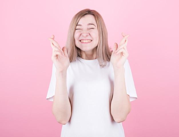 Erfreute fröhliche blonde frau unternimmt alle anstrengungen, um viel glück zu wünschen, drückt die daumen, isoliert über rosa wand.