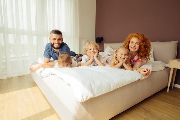 Erfreute glückliche familie, die zusammen auf dem bett ruht