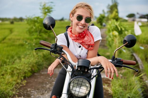 Erfreute glückliche frau sitzt auf ihrem motorrad, freut sich, den biker-wettbewerb zu gewinnen, ist zufrieden mit guten ergebnissen, mag hohe geschwindigkeit und bewegung im freien. menschen, aktiver lebensstil und outdoor-aktivitäten