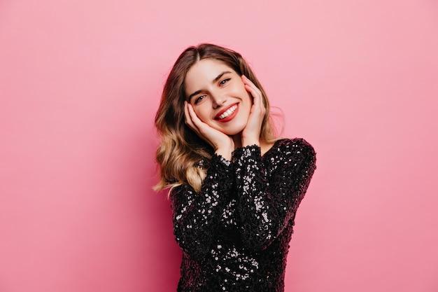 Erfreute gutaussehende frau posiert mit aufrichtigem lächeln. innenporträt des niedlichen europäischen mädchens lokalisiert auf rosa wand.