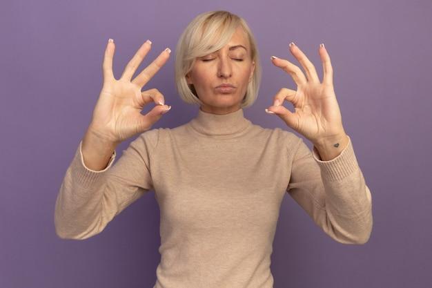 Erfreute hübsche blonde slawische frau gibt vor, über purpur zu meditieren
