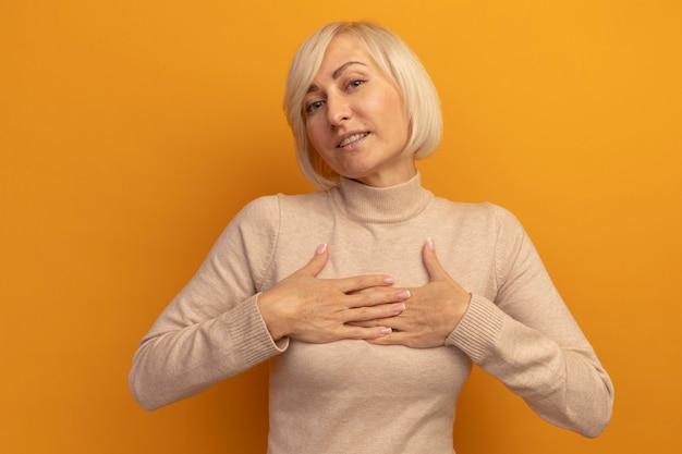 Erfreute hübsche blonde slawische frau legt hände auf orange auf die brust