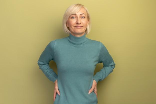 Erfreute hübsche blonde slawische frau legt hände auf taille und schaut kamera auf olivgrün