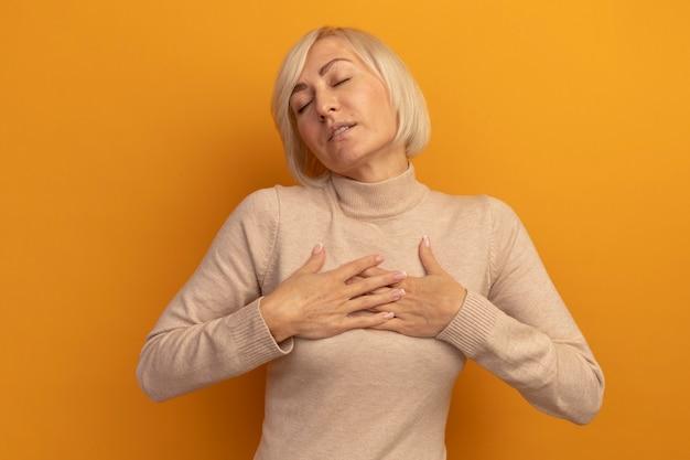 Erfreute hübsche blonde slawische frau mit geschlossenen augen legt hände auf orange auf die brust