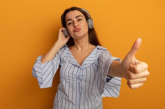 Erfreute hübsche frau auf kopfhörern daumen hoch isoliert auf orange wand