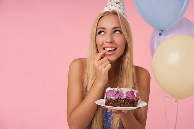 Erfreute hübsche frau, die sich freut, während sie in bunten luftballons posiert, geburtstag mit köstlichem kuchen feiert, positiv beiseite schaut und von zukunft träumt, lokalisiert über rosa hintergrund