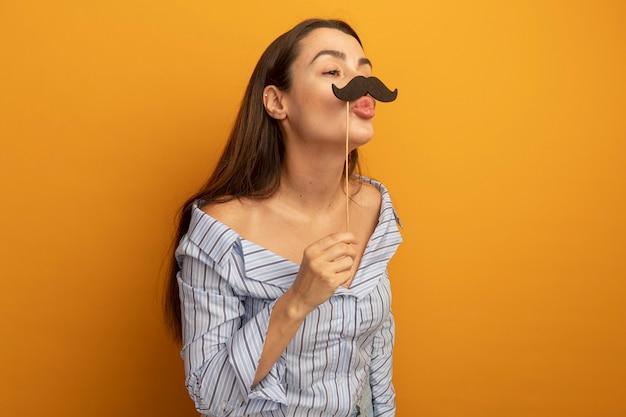 Erfreute hübsche frau hält falschen schnurrbart auf stock, der seite betrachtet, die auf orange wand lokalisiert ist