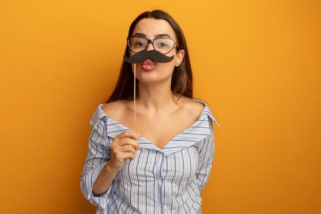 Erfreute hübsche frau in der optischen brille hält falschen schnurrbart auf stock lokalisiert auf orange wand
