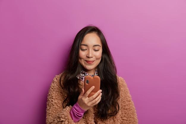 Erfreute hübsche junge asiatische frau mit dunklen haaren, liest interessante nachrichten, hat gadgetsucht, freut sich über nachricht, gekleidet in braunen mantel