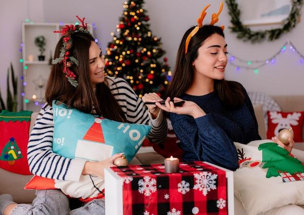 Erfreute hübsche junge mädchen mit stechpalmenkranz und rentierstirnband halten glaskugelverzierungen und telefon sitzen auf sesseln und genießen weihnachtszeit zu hause