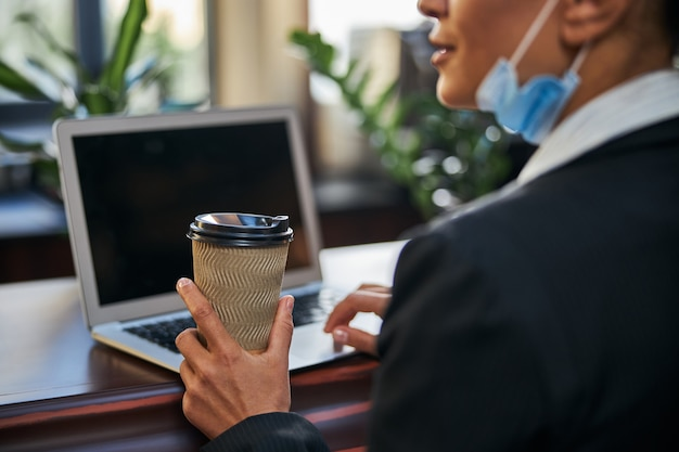 Erfreute internationale weibliche person, die vor ihrem laptop sitzt und pappbecher mit kaffee hält