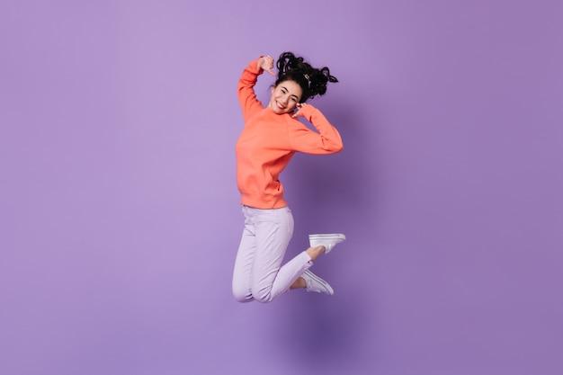 Erfreute japanische frau, die auf lila hintergrund springt. studioaufnahme der glückseligen asiatischen jungen frau.