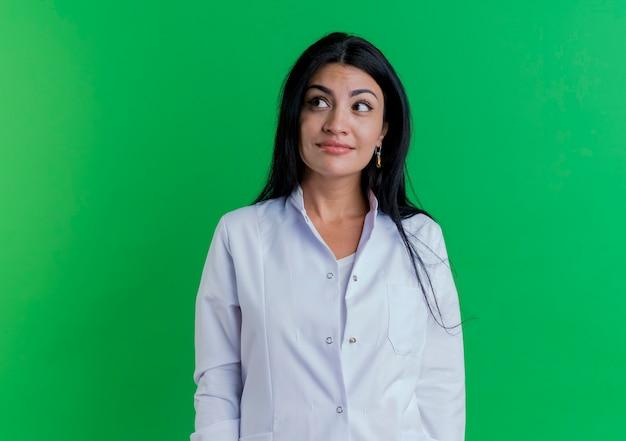 Erfreute junge ärztin, die medizinische robe trägt, die seite lokalisiert auf grüner wand mit kopienraum betrachtet