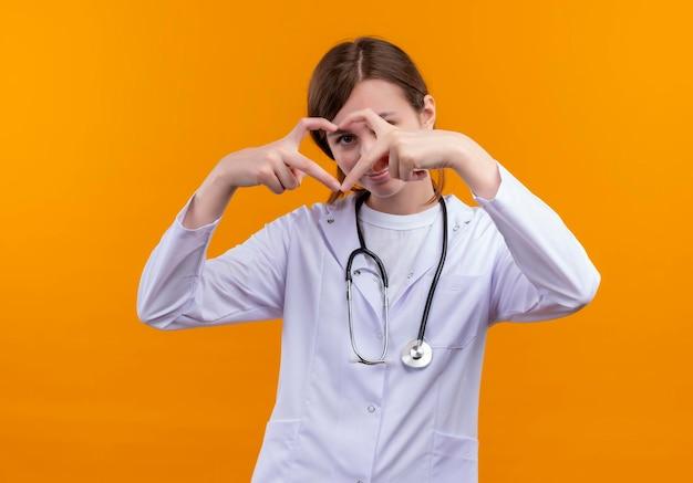 Erfreute junge ärztin, die medizinische robe und stethoskop trägt, die herzzeichen tun und durch es auf isoliertem orange raum schauen