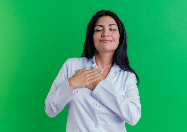 Erfreute junge ärztin im medizinischen gewand, die hände mit geschlossenen augen auf die brust legt