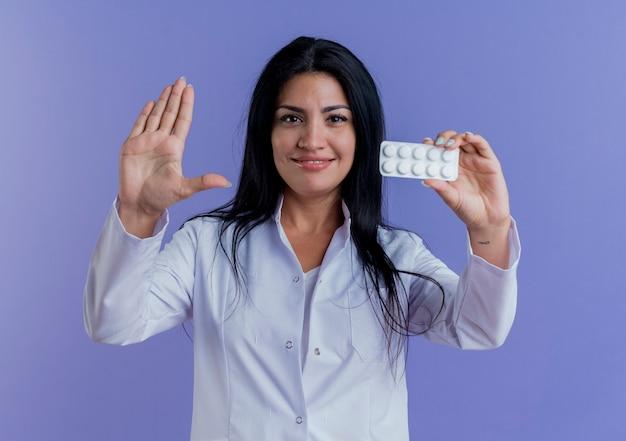 Erfreute junge ärztin in medizinischer robe, die eine packung medizinischer tabletten zeigt und dabei eine stoppgeste tut