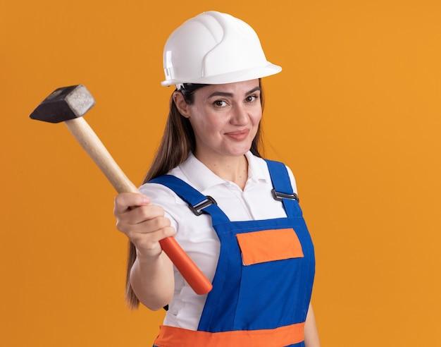 Erfreute junge baumeisterin in uniform, die den hammer in die kamera hält, die auf orangefarbener wand isoliert ist?