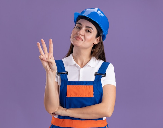 Erfreute junge baumeisterin in uniform, die drei lokalisierte auf lila wand zeigt