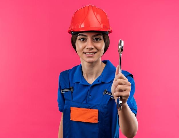 Erfreute junge baumeisterin in uniform, die einen gabelschlüssel isoliert auf rosa wand hält