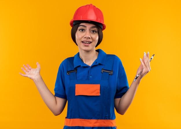 Erfreute junge baumeisterin in uniform, die einen maulschlüssel hält, der die hände isoliert auf der gelben wand ausbreitet