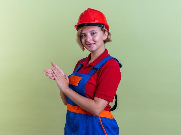 Erfreute junge baumeisterin in uniform, die händchen hält, isoliert auf olivgrüner wand