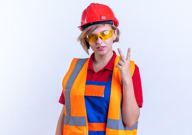 Erfreute junge baumeisterin in uniform mit brille, die friedensgeste isoliert auf weißer wand zeigt