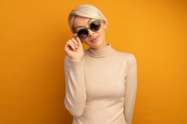 Erfreute junge blonde frau, die eine sonnenbrille trägt und greift, die vorne isoliert auf oranger wand mit kopienraum schaut
