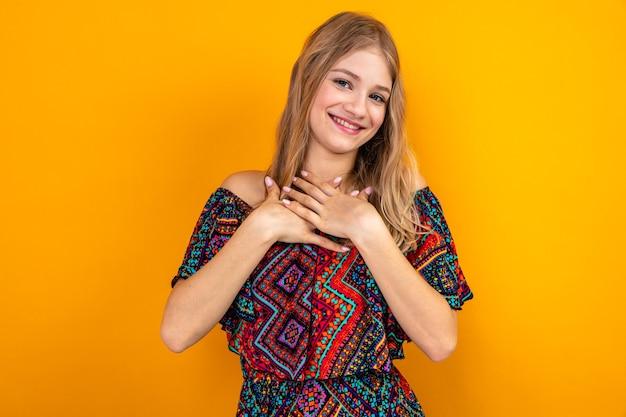 Erfreute junge blonde frau, die hände auf ihre brust legt