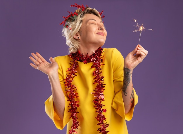 Erfreute junge blonde frau, die weihnachtskopfkranz und lametta-girlande um den hals hält, die feiertagswunderkerze zeigt, die leere hand mit geschlossenen augen lokalisiert auf lila hintergrund zeigt